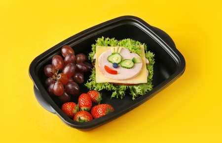 Tasty sandwich and fruits in lunchbox on yellow background