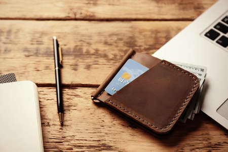 Workplace with stylish leather wallet and laptop