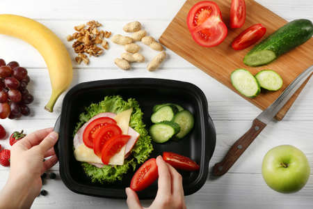 Female hands packing dinner in lunchbox on white wooden table