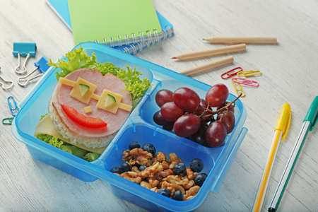 Tasty sandwich and fruits in lunchbox and stationery on light wooden background