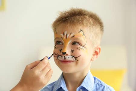 Vrouwelijke hand schilderij gezicht van grappige jongen