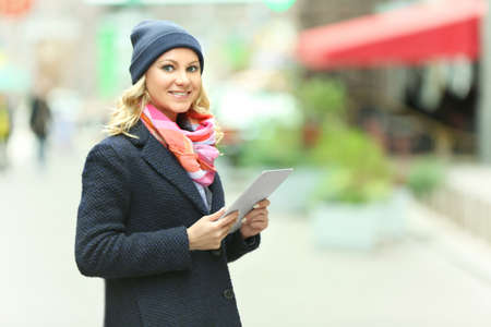 Young woman with tablet on city street background