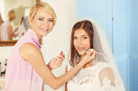 Preparazione del matrimonio. Truccatore professionista che applica lucidalabbra sulle labbra della sposa% 00