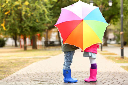 Children hiding behind colorful umbrella in park Stock Photo