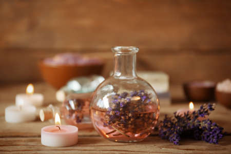 Spa concept. Bottle with lavender aroma oil and candles on wooden background Stock Photo