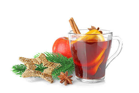 Glass cup of delicious mulled wine with Christmas decor on white background