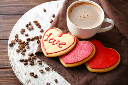 Heart shaped cookies with cup of coffee and beans on wooden table, closeup