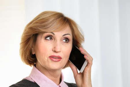 Portrait of senior businesswoman talking by mobile phone, on light background