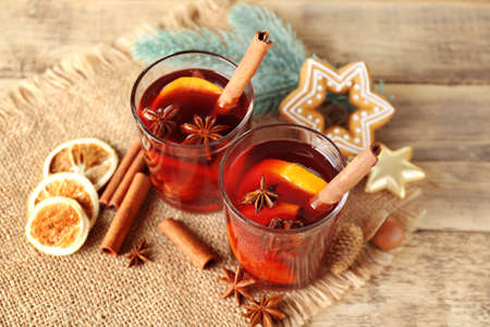 Glasses of delicious Christmas mulled wine on sackcloth, closeup
