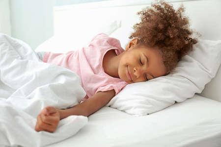Weinig Afrikaans Amerikaans meisje dat in bed rust Stockfoto
