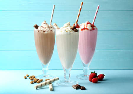 Delicious milkshakes on blue wooden background