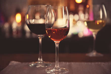Two glasses with tasty wine in bar on bright background Stock Photo