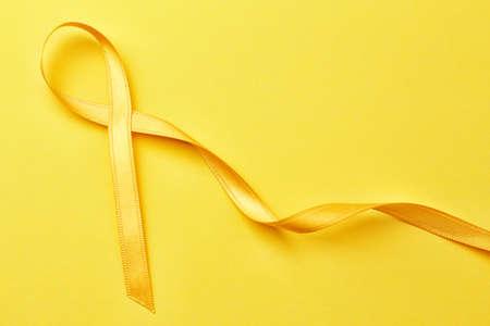 Golden ribbon on color background. Children cancer concept