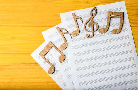 Notas musicales sobre hojas de música sobre fondo de madera amarilla