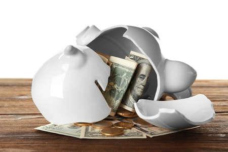 Broken piggy bank with money on white background 스톡 콘텐츠