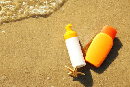 Lotion bottles with starfish on beach sand