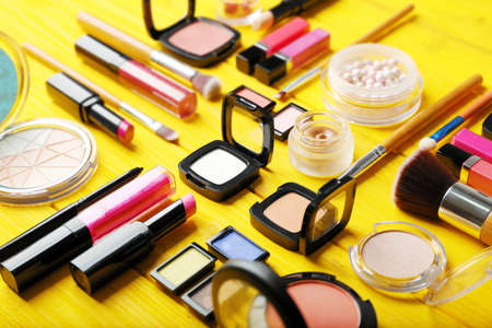 Flat lay of makeup cosmetics on yellow background Imagens