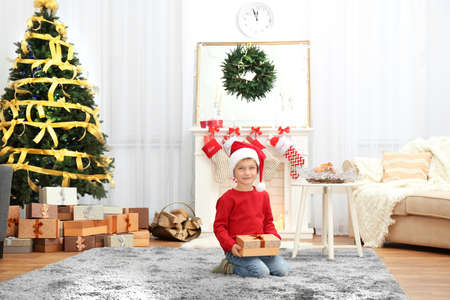 Cute little boy in Santa hat with Christmas present at home Stock Photo