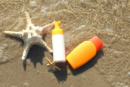 Lotion bottles with starfishes on beach sand Stock Photo