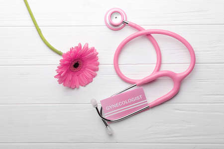 Business card with word GYNECOLOGIST, flower and stethoscope on white wooden background