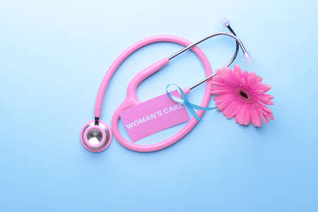 Business card with text WOMANS CARE, ribbon, flower and stethoscope on blue background Stock Photo