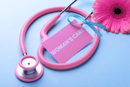 Business card with text WOMANS CARE, ribbon, flower and stethoscope on blue background