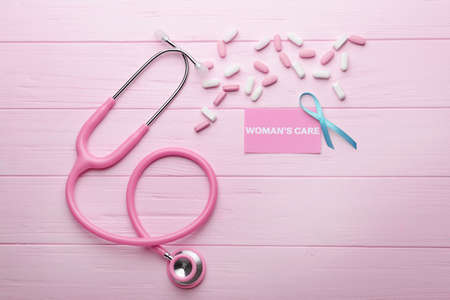 Business card with text WOMANS CARE, ribbon and stethoscope on pink wooden background
