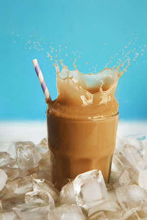 Glass of cold coffee with ice cubes and splashes on table Imagens