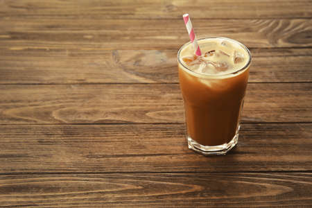 Glass of cold coffee on wooden background