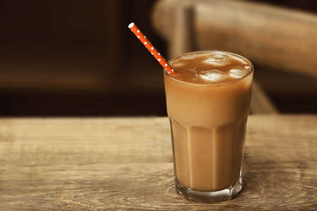 Glass of cold coffee on wooden table Stock Photo