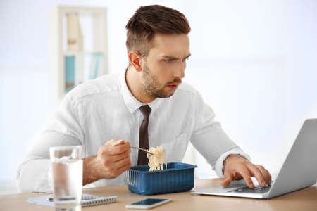 Jonge mens die onmiddellijke noedels eet terwijl het werken met laptop in bureau