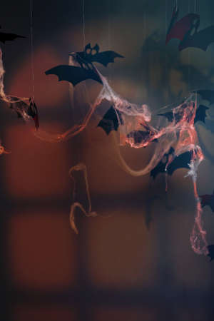 Paper bats and spider web on dark background as Halloween decor
