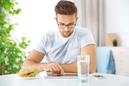 Young man having snack while working with tablet computer in kitchen Stock Photo