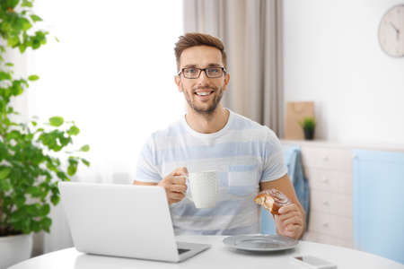 Young man having snack while working with laptop in kitchen Stock Photo