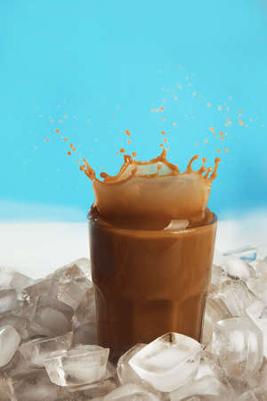 Glass of cold coffee with ice cubes and splashes on table Stock Photo