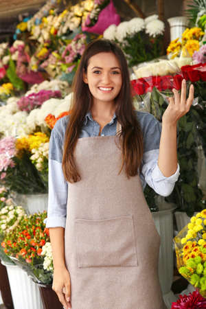 Pretty young florist in flower shop