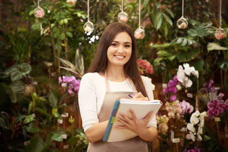 Pretty young florist with notebook and pen in greenhouse Stock Photo