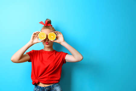 Young beautiful woman with oranges on blue background