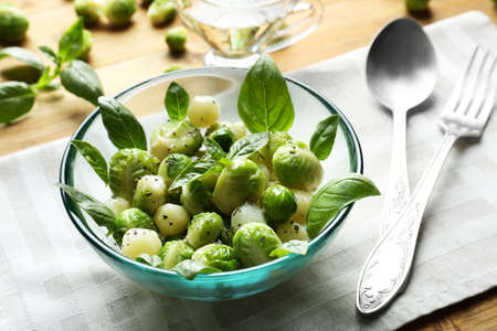 Bowl with delicious salad of Brussels sprouts and basil on table Stock Photo