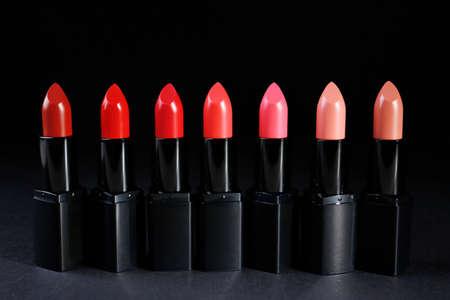 Many lipsticks on dark background