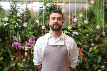 Handsome bearded florist in greenhouse