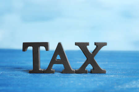 Word TAX on blue wooden surface, close up view