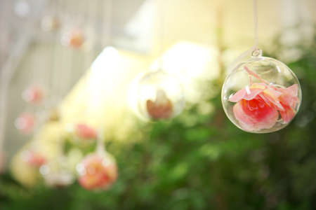Close up view of decorative glass ball with flower inside, on blurred background