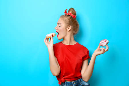 Young beautiful woman with doughnuts on blue background