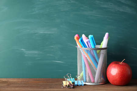 Colorful school stationery on table on blackboard background Stock Photo