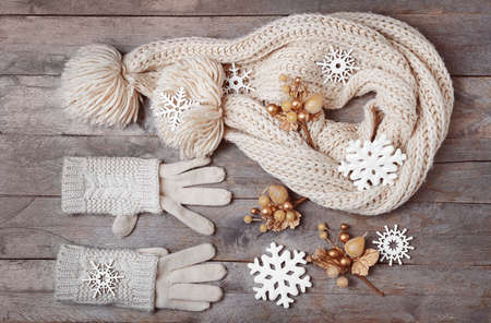 Knitted gloves, scarf and Christmas decor on wooden background Foto de archivo