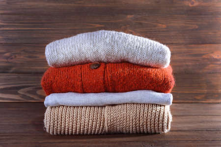 Stack of warm winter clothes on wooden background