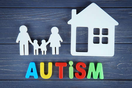 Word AUTISM with family and house on wooden background