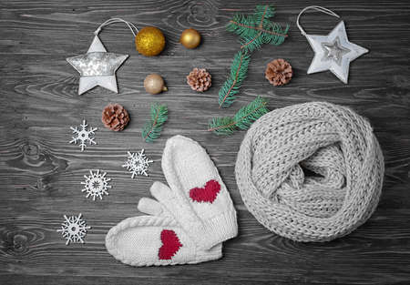Knitted scarf, mittens and Christmas decor on wooden background Foto de archivo