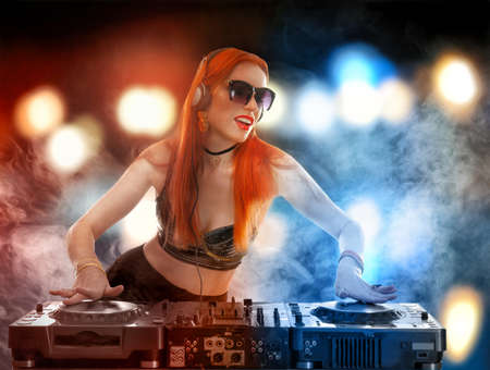 DJ mixing music on blurred lights background
